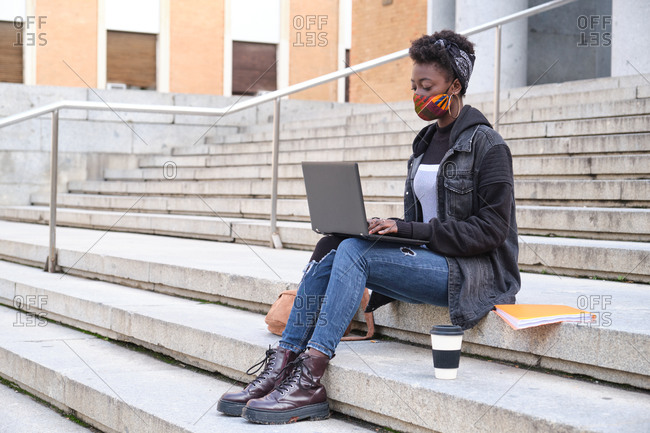 University female african student wearing protective face mask studying on her laptop sitting on stairs outside on campus. New normal in college.