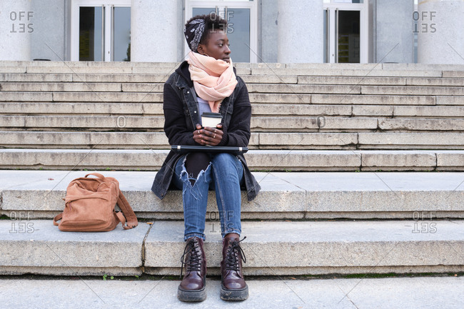 Beautiful university female african student looking at side, holding a cup of coffee, sitting on stairs outside on campus. College life concept.