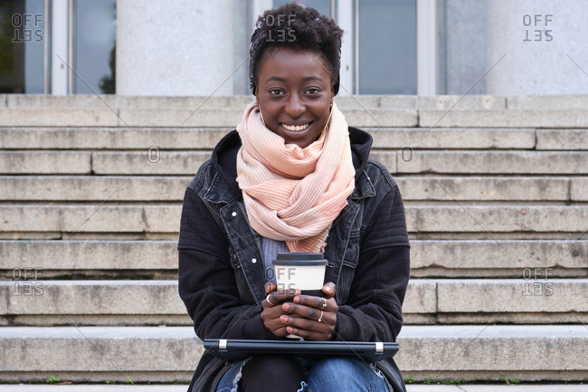 Beautiful university female african student smiling looking at camera, holding a cup of coffee, sitting on stairs outside on campus. College life concept.
