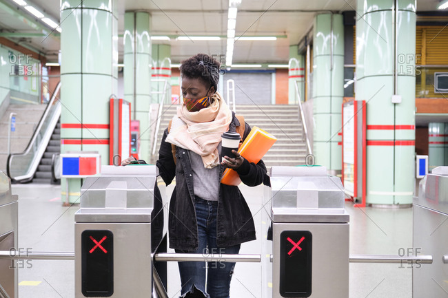 University female african student wearing protective face mask passing through the turnstiles with her transport card at the underground station. New normal in public transport.