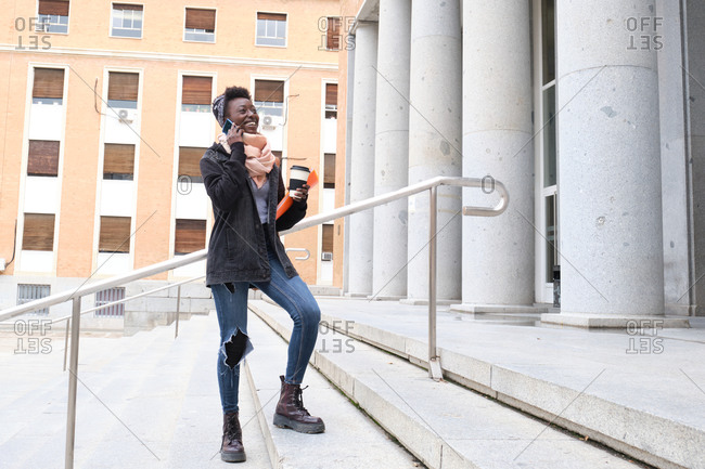 University female african student laughing and speaking on her smartphone, holding a coffee cup on the stairs of the school building on campus. College life concept.