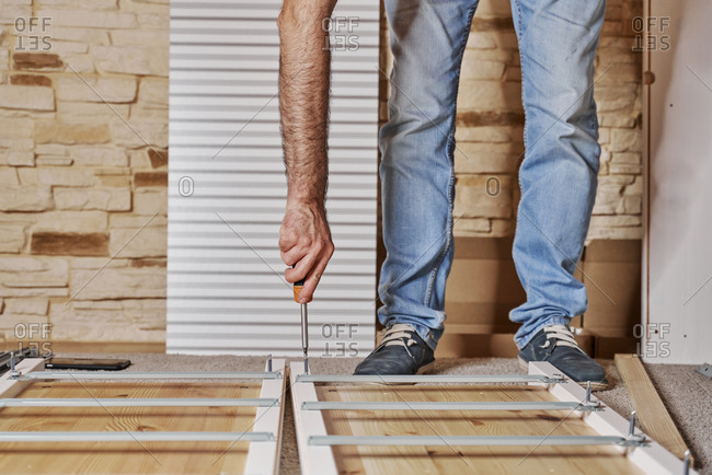 Front view of a unrecognized worker screwing a screw with a screwdriver in a strip of a furniture assembling by himself a wardrobe of wood. Horizontal photo.