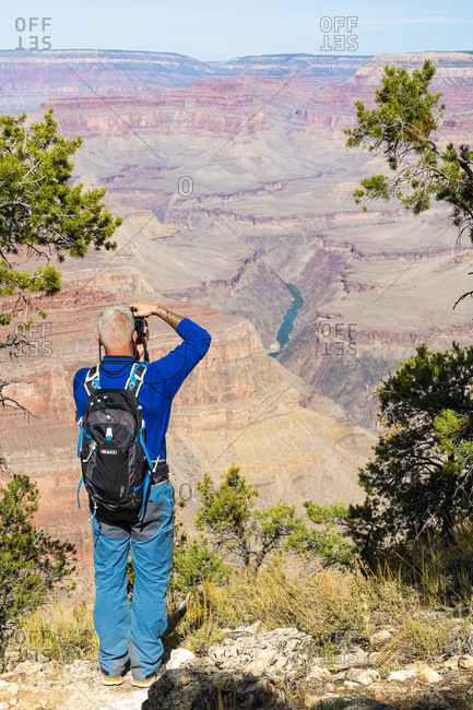 United States, Arizona, Grand Canyon Village - October 21, 2019: Idyllic shot of male tourist taking picture of Grand Canyon along Hermit Road, Grand Canyon National Park, Arizona, USA