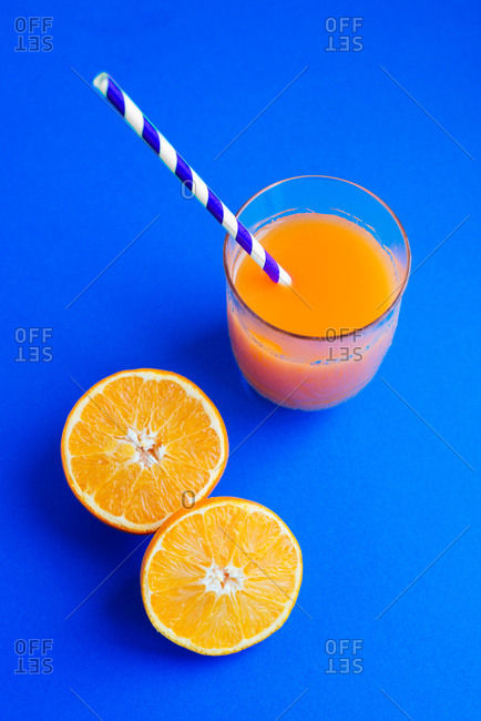 Freshly squeezed orange juice on blue background