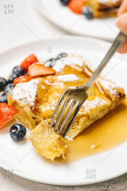 Fork in French Toast Casserole with maple syrup and berries