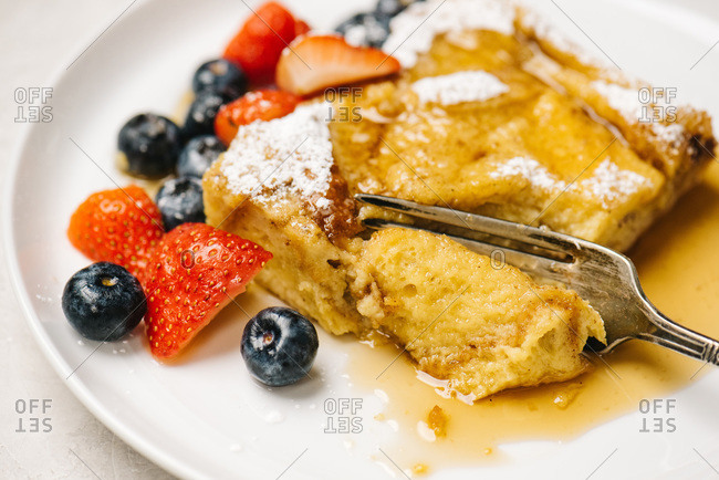 Fork cutting into French Toast Casserole with maple syrup and berries
