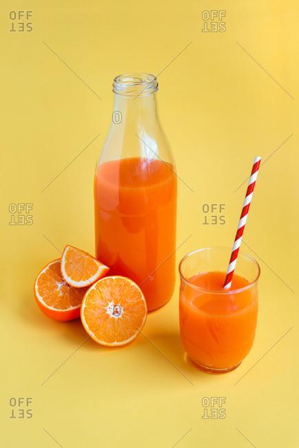 Freshly squeezed orange juice on yellow background