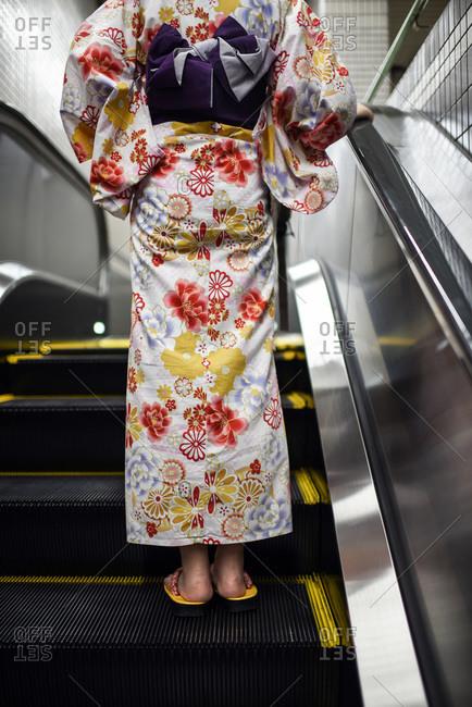 Young woman wearing a Japanese kimono in escalator