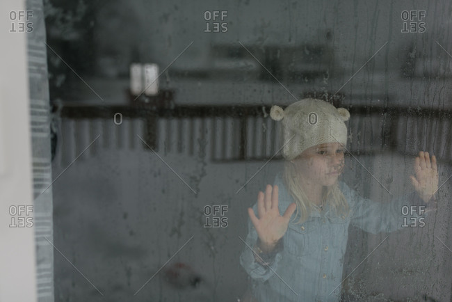 Little girl looking out large window at snow