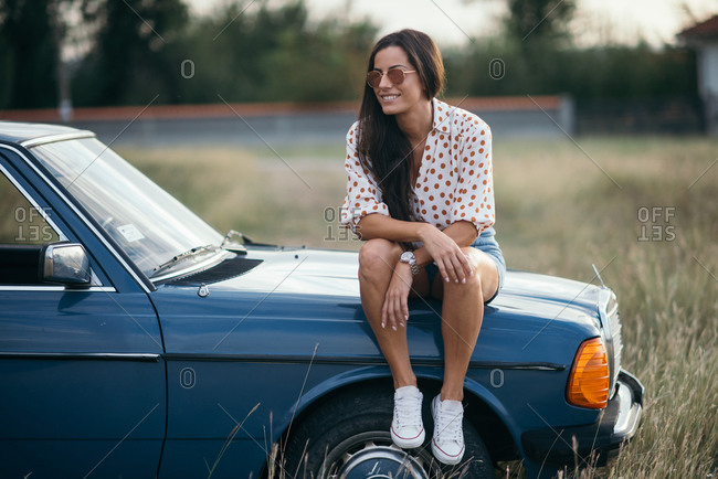 Smiling woman sitting on the car