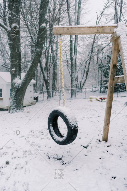 dreary dark wintery backyard swing with tire covered in fresh snow