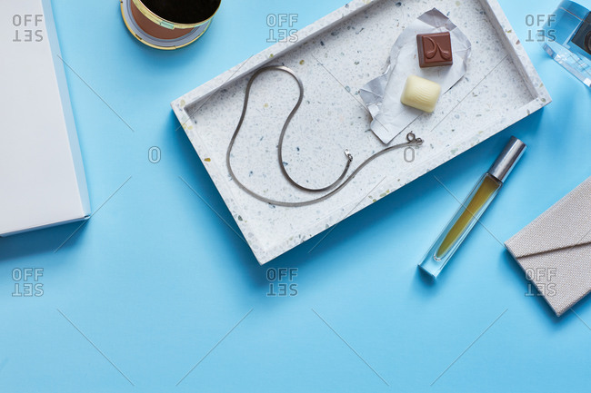 Chocolates, necklace, perfume on Turquoise surface