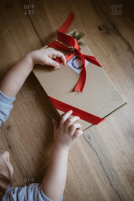 Little girl opens presents at a table.