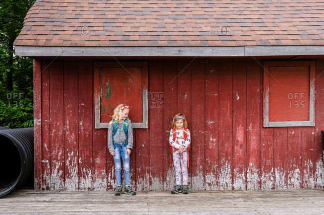 two girls standing together against weathered red barn wall
