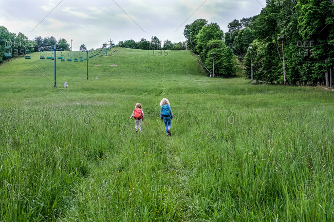 two girls walking in distance up large hill while hiking in spring