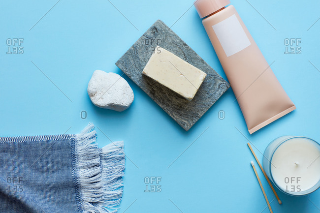 Soap, cream, candle on turquoise surface
