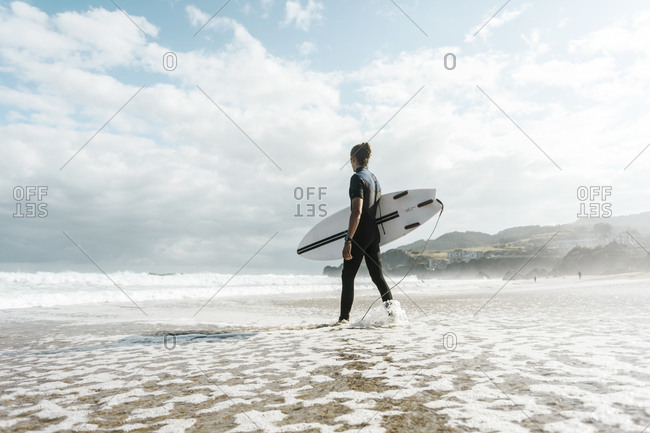 Surfer entering the water in the Basque country, Spain, Bilbao