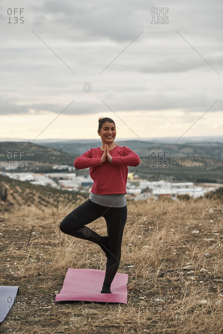 A young woman practices Yoga at sunset