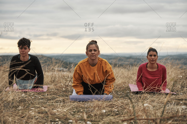 3 young women practicing pilates outdoors