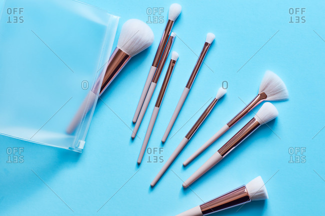 Assortment of Makeup brushes on turquoise surface