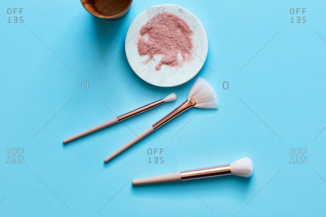 Makeup powder and brushes on turquoise surface
