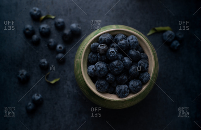 Bowl of fresh ripe blueberries on dark background. Top view