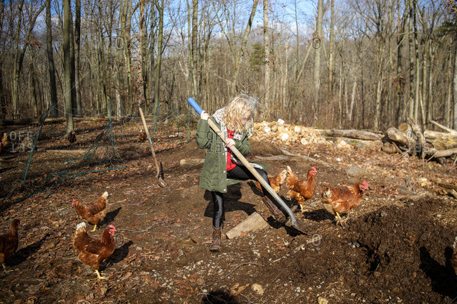 Girl with blonde hair digging with shovel on farm with chickens