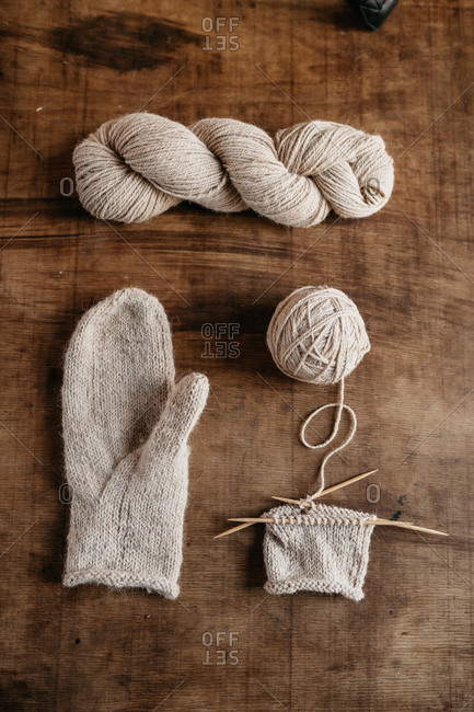 knitted mitten with skein of Alpaca yarn on wooden table