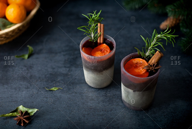 Mulled red wine in glasses with spices, rosemary, cinnamon and oranges