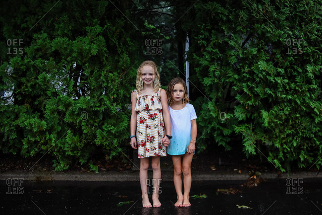 portrait of two girls standing in the rain