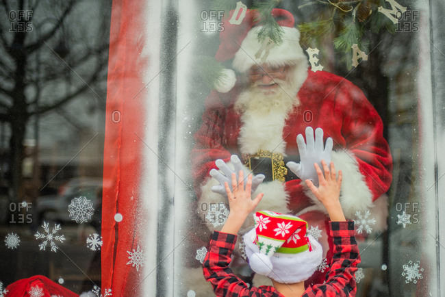 Young Boy connects with Santa in window