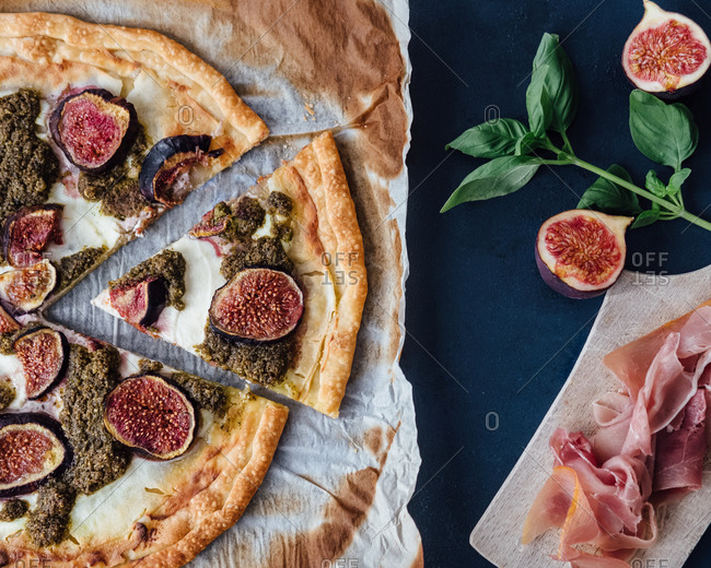 Top down view of ricotta, fig and pesto pizza with prosciutto
