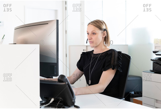 a medical secretary writes a report on her computer