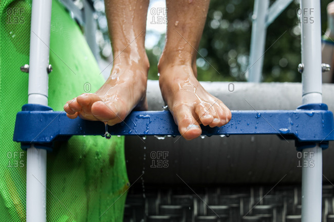 close up of wet feet standing on pool ladder with water dripping off