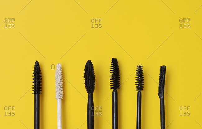 Various types of mascara wands on yellow surface