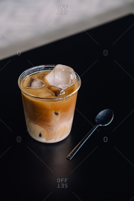 Specialty coffee iced latte on black tabletop with black spoon