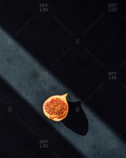 Minimal photo of a fig half on dark background in a ray of light