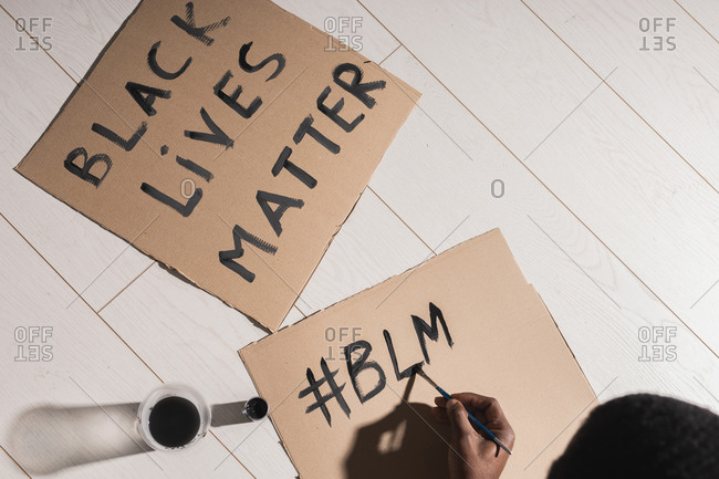 Black man writing poster Black Lives Matter, social movement.