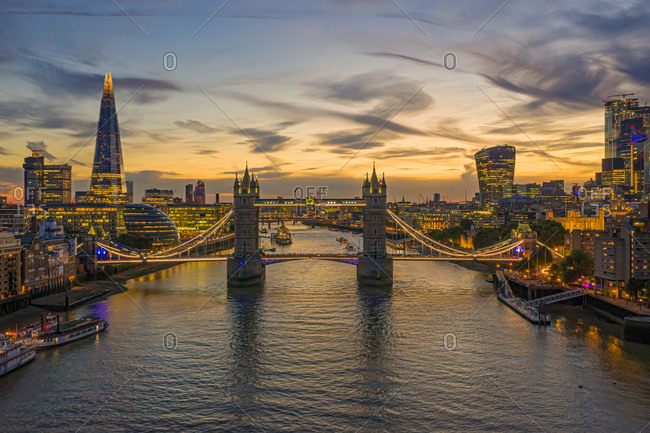Aerial view of London bridge crossing the river Thames at sunset, United Kingdom.
