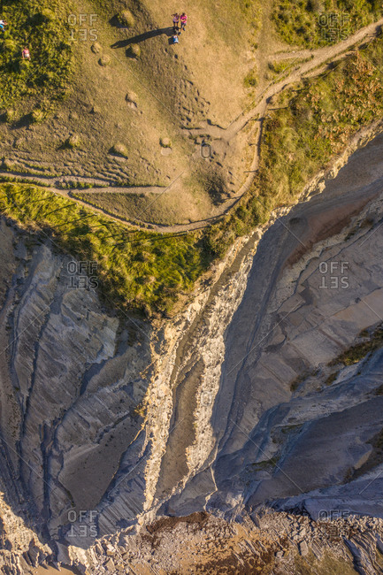 Aerial view of few tourists standing on the cliff near Sakoneta beach in Deba, Gipuzkoa state, Spain.