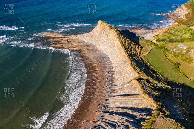 Aerial view of Atlantic Ocean waves breaking on Sakoneta beach near the city of Deba in Euskadi state, Spain.