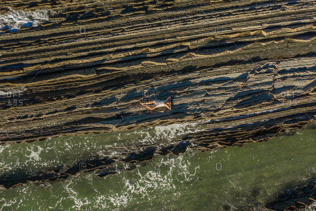 Aerial view of two people standing on a curious rock formation promontory in Gipuzkoa, Euskadi, Spain.
