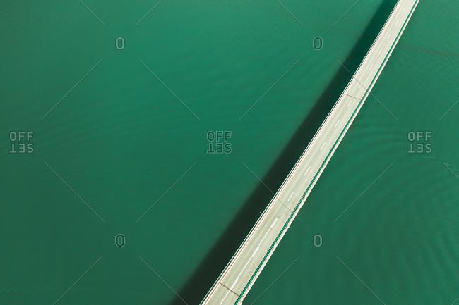 Aerial view of a car driving on the bridge crossing Pantà de la Baells lake near Cercs, Catalonia, Spain.