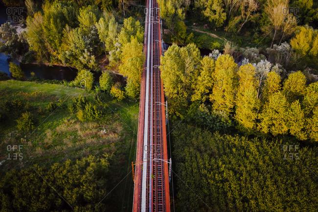 Aerial view of train rail road crossing the countryside near Flaca township, Girona, Spain.