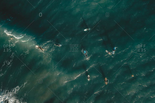 Aerial view of people surfing the waves in the ocean near Sakoneta beach in Gipuzkoa, Euskadi, Spain.