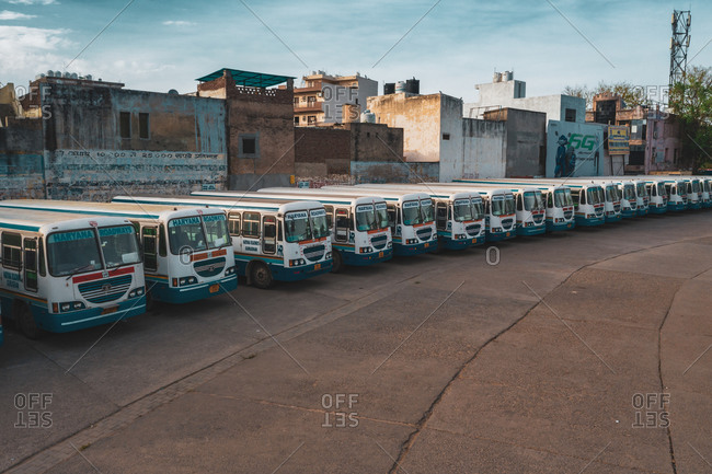 April 16, 2020: Gurugram, India16 April 2020: Aerial view of a line of public buses parked in a parking lot in Gurugram during lockdown, Haryana state, India.