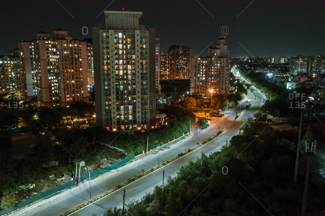 Aerial view of tall skyscraper in Gurugram near the motorway and the railway at night. Haryana state during lockdown, India.
