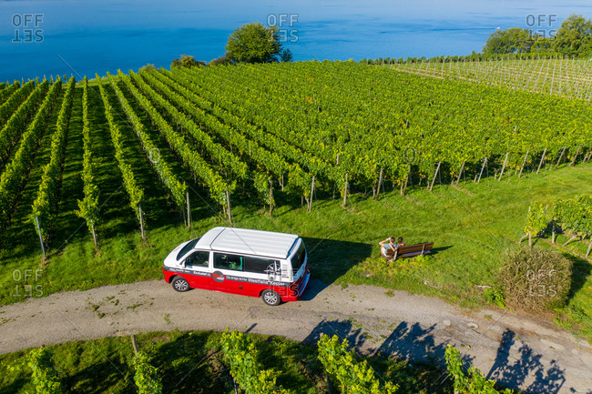 September 8, 2020: Aerial view of a camper van driving a small road with vineyard along the Constance lake, Germany.