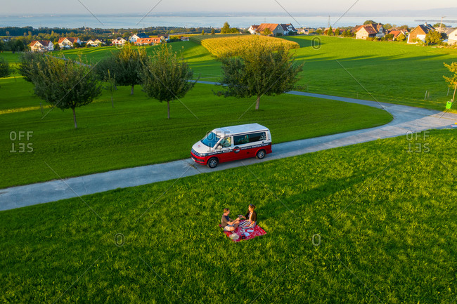 September 9, 2020: Morschwil, Switzerland9 September 2020: Aerial view of two people having a picnic on the grass next to their motorhome. Morschwil, Switzerland.