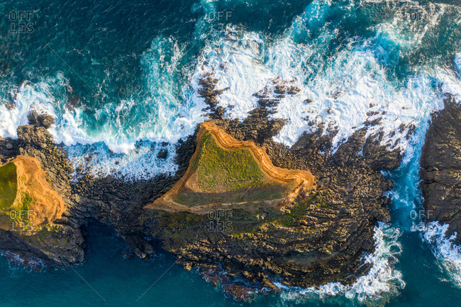 Aerial view of the crispy waves breaking on the rocks at Sao Miguel Island, Azores archipelagos, Portugal.